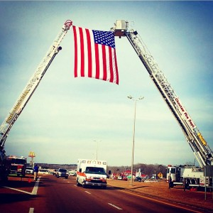 The ambulance carrying paramedic Andy Sharp on his last ride as it passes under a United States flag held in place by ladder units from the Philadelphia (Mississippi) and Choctaw Fire Departments. Credit: Brandi Smith-Wyatt